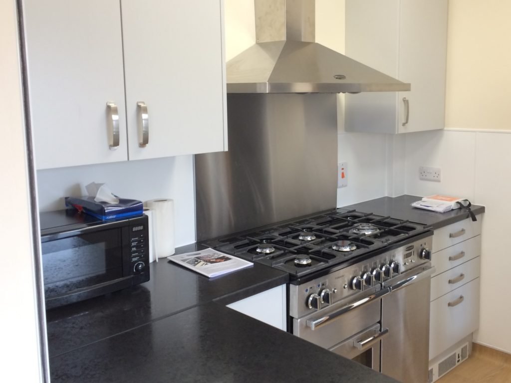 a view of the kitchen including the 5 ring gas hob and combination double oven