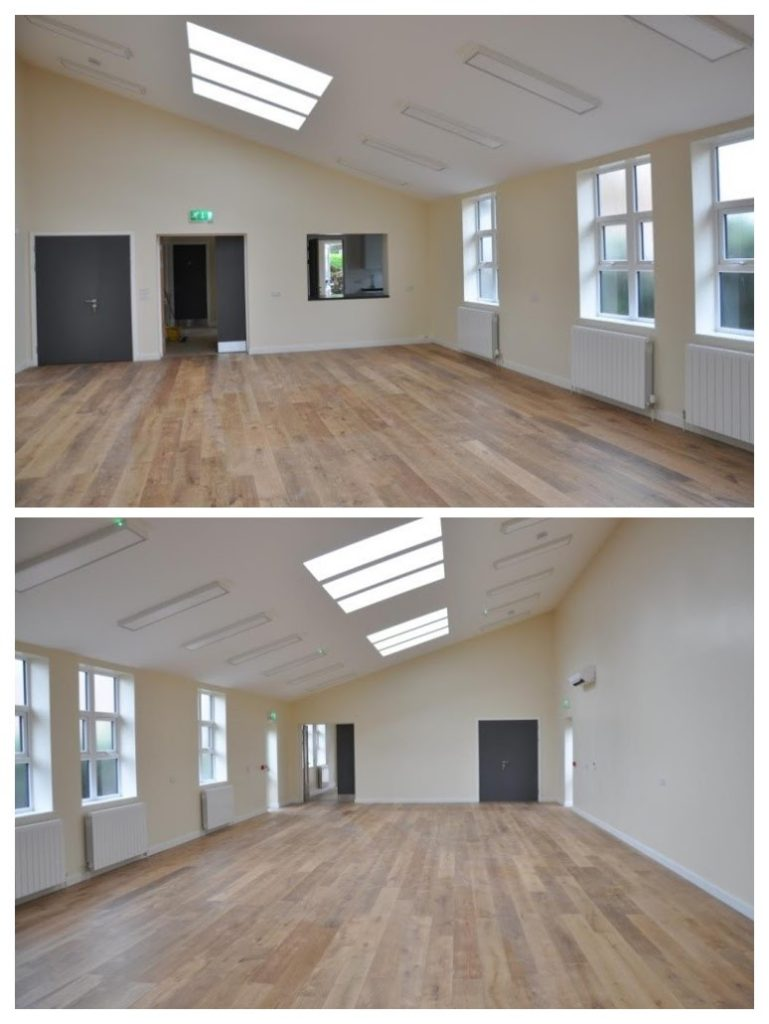 A view of the main hall showing the wooden floor, windows, skylights, airconditioning, radiators and lights